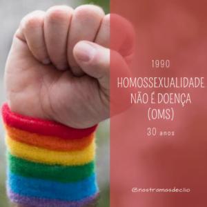 Punho cerrado com munhequeira nas cores do arco íris. Com a frase em destaque: homossexualidade não é doença.